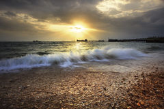 Splashing sea wave on gravel beach against sun set sky and comme Stock Image