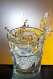 Splashing spirit. Photo of glass on table in which enters ice cube so it splashes around Royalty Free Stock Images