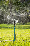 Splashing from a sprinkler on the garden Royalty Free Stock Photo