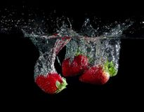 Splashing strawberries stock images