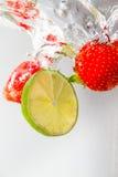 Splashing Strawberry and Lime. Fresh strawberry and lime slice splashing into water Stock Photo