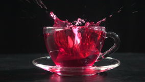 Splashing a teabag in transparent cup of tea, slow motion. Splashing a teabag in transparent cup of tea in on black background, slow motion 250 fps stock video footage