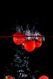Splashing tomatoes into a water Royalty Free Stock Images