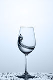Splashing transparent water wave in the wine glass while standing on the glass against light background. Splashing transparent water wave in the wine glass Royalty Free Stock Photos