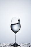 Splashing transparent water wave in the wine glass while standing on the glass with droplets against light background. Pure and cleaner water. Natural and Stock Photography
