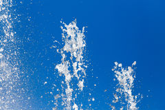 Splashing water against the blue sky Stock Photography