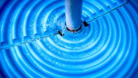 Splashing Water on Blue Round Grooved Bath for Decoration Stock Image