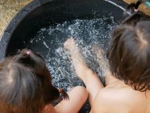 Splashing water in a bucket, as the two little Asian baby girls, sisters, playing together in a rural area of Thailand. Baby sisters` friendship royalty free stock photo