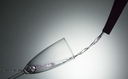 Splashing water. Champagne glass with violet water Royalty Free Stock Photography