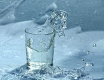 Splashing water from glass. Water splashing out of the glass royalty free stock photos