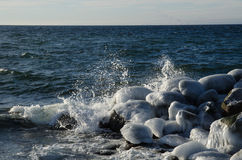 Splashing water at icy rocks Stock Image