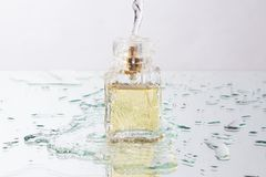 Splashing water on perfume bottle stock photography