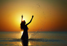 Splashing water in the rays of dawn. Silhouette of woman making splashes in the rays of the rising sun. Horizontal photo Stock Images