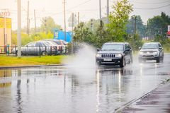 Splashing water on the road from the car. Summer rain. Puddles on the road. Russian roads. Wet street. Russia, Leningrad region stock images