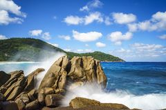 Water fountain over granite rocks,wild tropical beach with palms Royalty Free Stock Photo