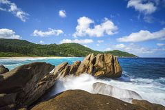 Water fountain over granite rocks,wild tropical beach with palms Stock Photos