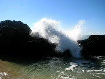 Splashing wave. A large amount of spray caused by a wave crashing against the rocks royalty free stock images