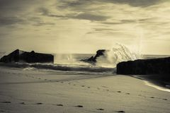 Huge splashing wave of atlantic ocean against blockhouse silhouette in sunset sky in black and white with yellow filter, capbreton Royalty Free Stock Photos