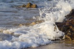 Splashing wave while hitting the rock at the beach Stock Photos