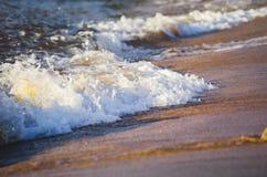 Splashing wave while hitting the rock at the beach Royalty Free Stock Image