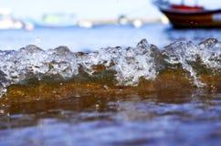 Splashing wave while hitting the rock at the beach Stock Photo