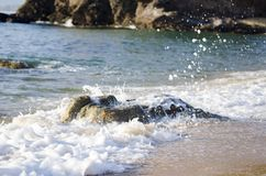 Splashing wave while hitting the rock at the beach Royalty Free Stock Images