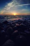 Splashing waves on the beach of round stones at sunset Stock Photo