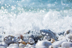 Splashing waves over pebbles Stock Photography