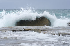 Splashing waves on rock in ocean Stock Photography