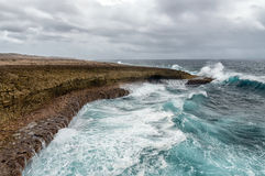 Splashing waves at a rough and rocky coastline Royalty Free Stock Photos