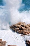 Splashing waves. Sea waves splashing over a rocky shore Stock Image