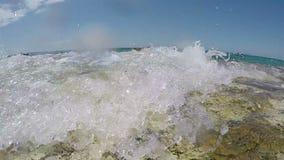 Splashing waves. Slow motion shot of splashing sea wave on stone Adriatic beach stock footage