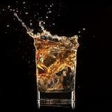 Splashing whiskey. Isolated shot of whiskey with splash on black background Stock Photo