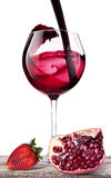 Splashing wine with pomegranate and strawberry Royalty Free Stock Image
