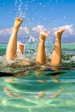 Splashy. Feet out of water the two girls are plaing around in the ocean Royalty Free Stock Photography