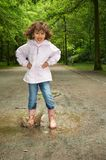 Splashy fun. Little girl making a big splash in a water puddle Stock Photo