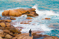 Splashy waves on the rocks. A photographer is surveying the rocky splashy waves at Shek-O beach in hong kong Royalty Free Stock Images