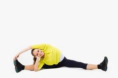 spleet Jonge vrouw die uitrekkende oefening doet Op wit Royalty-vrije Stock Afbeelding