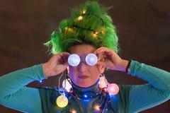 Splended dziewczyna z zielonym włosy ubierał w Bożenarodzeniowych girlandach Dziewczyna przedstawia choinki Pojęcie dobry nastrój zdjęcia stock