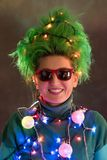 Splended girl with green hair dressed in Christmas garlands. A girl is depicting a Christmas tree. The concept of a good mood on a. Holiday Royalty Free Stock Images