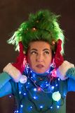 Splended girl with green hair dressed in Christmas garlands. A girl is depicting a Christmas tree. The concept of a good mood on a. Holiday Royalty Free Stock Photography