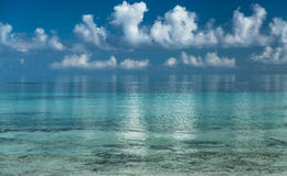 Splendid amazing inviting view of early morning ocean and white fluffy clouds reflected in water background Stock Image