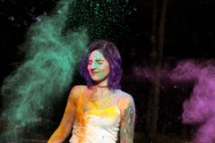 Splendid brunette woman with tattoo covered with dry Holi powder Royalty Free Stock Photo