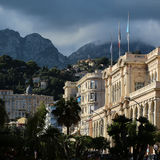 Splendid palais de leurope. Menton. France - Month09.2015: Picturesque sight of splendid palais de leurope building surrounded by green palms on natural Royalty Free Stock Image