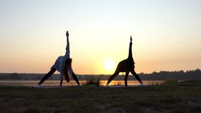 Splendid Sunset And Women Doing Yoga Exercise on a Lake Bank in Slo-Mo. Two Slender Young Women Bend Forward, Touch Land With One Hand, Raise the Second Hand on stock footage