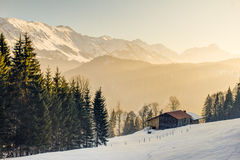 Splendid view from wooden cabin to the mountains of Allgäu. Panoramic view from a wooden cabin to the mountains covered in orange light Royalty Free Stock Photos