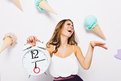 Splendid young woman in white tank-top posing with eyes closed holding clock on decorated background. Studio portrait of. Excited brunette girl laughing stock photo
