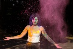 Splendid woman with purple hair tossing up pink Holi powder Stock Photography