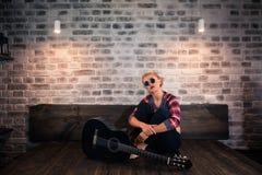 Splendor blondynki dziewczyna w kauzalnych ubraniach siedzi na łóżku z gitarą w wygodnym mieszkaniu zdjęcia royalty free