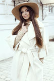 Splendor dziewczyna z ciemnym prostym włosy jest ubranym luksusowego beżowego żakiet z eleganckim kapeluszem, Obrazy Stock